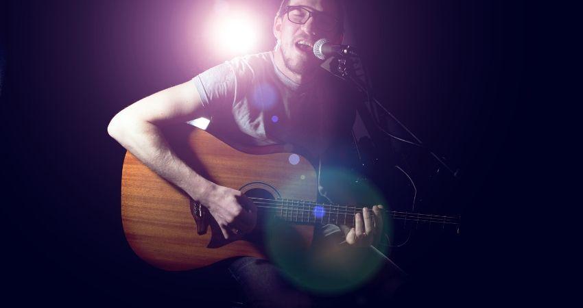 Homem tocando um acorde no violão